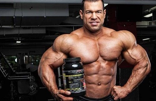 Bodybuilder Holding Supplements